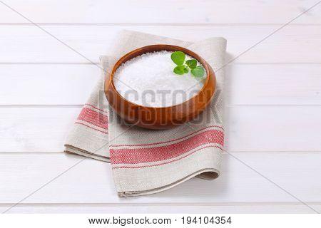 bowl of coarse grained sea salt on folded place mat
