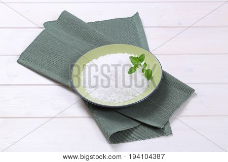plate of coarse grained sea salt on grey place mat