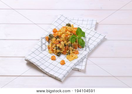 pile of raw colored pasta on checkered dishtowel