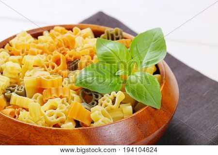 bowl of raw colored pasta on dark grey place mat - close up