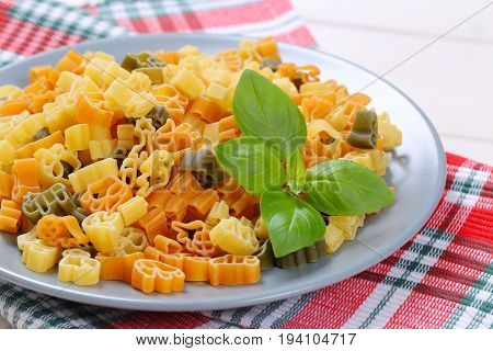bowl of raw colored pasta on checkered place mat - close up