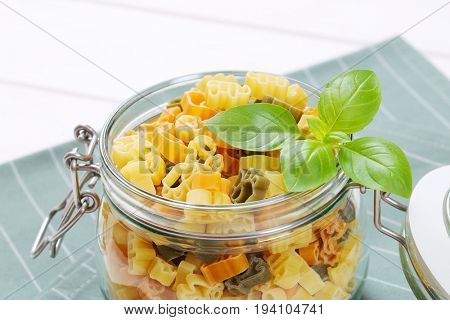 jar of raw colored pasta on grey place mat - close up