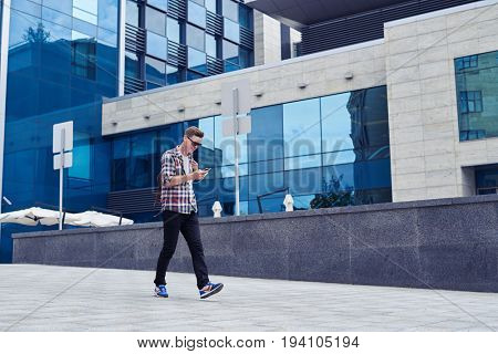 Wide shot of stylish young man listens to music and enjoys city panorama. Walking in front of business mall