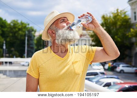 Close-up shot of thirsty bearded man drinking water on hot summer day