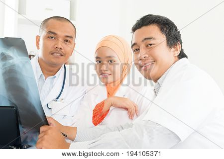 Medical team examining radiography in office. Southeast Asian Muslim doctors and nurses.