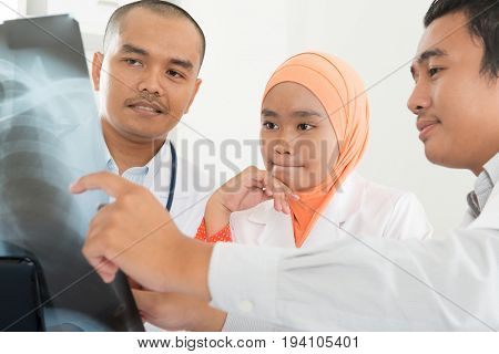 Group of doctors looking at x-ray scan image. Southeast Asian Muslim people.