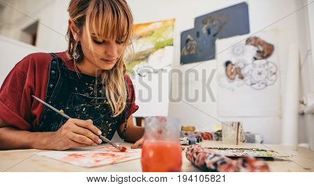 Shot of beautiful young female artist painting in studio. Woman painter drawing on paper in her workshop.