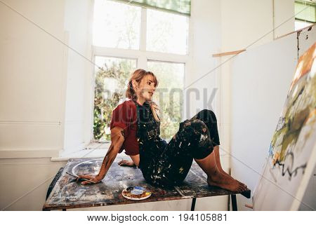 Indoor shot of female painter working in studio. Relaxed young woman artist looking at painting in her workshop and thinking.