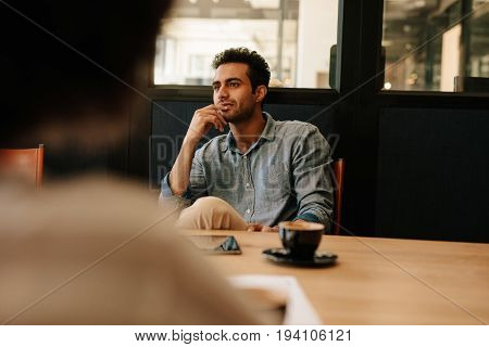 Handsome young man sitting at table in conference room and listening to colleague. Man during business meeting.