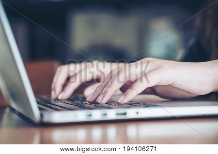 Closeup image of a business woman's hands working and typing on laptop keyboard on wooden table in office