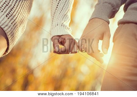Detail of a young couple in love holding hands and walking through a park on a sunny autumn day. Selective focus