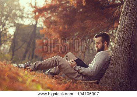 Handsome young man sitting on a fallen autumn leaves in a park reading a book