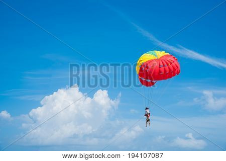 People enjoy parasailing water sport Flying on a parachute behind a boat on a summer holiday by the sea at Patong beach. The most famous tourist attraction in Phuket province Thailand.