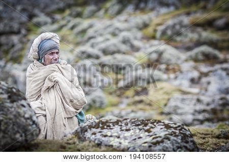 Gondar Ethiopia October 5th 2014: old Man wrapped in rags resting and looking at the view in Simien mountain