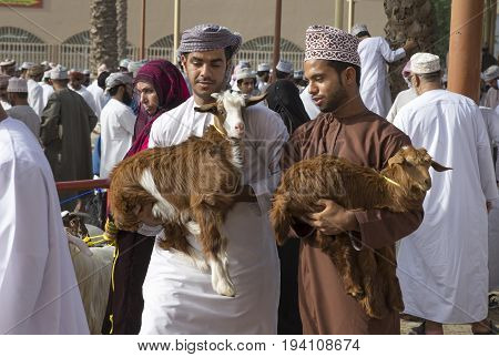 Nizwa Oman June 23rd 2017: omani men carrying goats at a Habta market