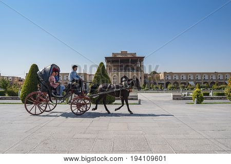 ISFAHAN IRAN - OCTOBER 22 2016 : Iranian tourists sit on carriage during visit the Naghsh-e Jahan Square (Imam Sqaure) UNESCO World Heritage Sites in Isfahan (Esfahan) Iran.