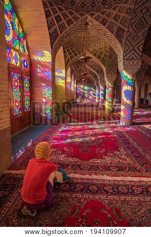SHIRAZ IRAN - OCTOBER 23 2016 : Unidentified woman traveler see the colorful light through stained glass window inside Nasir Al-Mulk (Pink Mosque) a traditional mosque in Shiraz Iran.