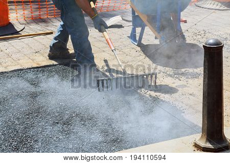 Construction Workers During Asphalting Road Works Wearing Coveralls.