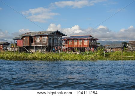 Traditional wood house with gable roof and green floating garden in the village on Inle lake located in the Nyaungshwe Township of Taunggyi Shan State Myanmar