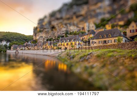 Beautiful sunset view on Dordogne river and famous La Roque Gageac village during the rainy weather in France. Tilt-shift image technic