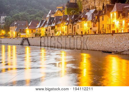Beautiful view on Dordogne river and illuminated La Roque Gageac village during the rainy weather in France
