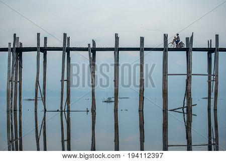 AMARAPURA MYANMAR - DECEMBER 24 2016 : Burmese woman and child ride a bicycle on U Bein Bridge the oldest and longest teak bridge (Wooden footbridge) in the world near Mandalay.