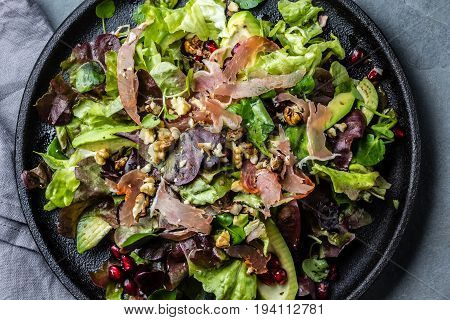 Lettuce Salad With Ham Serrano And Pomegranate. Top View