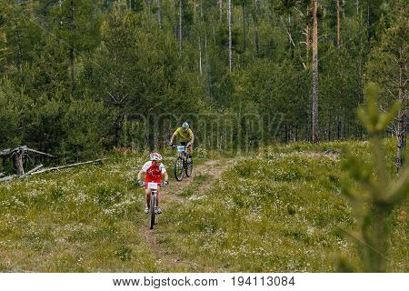 Revda Russia - July 1 2017: two cyclists ride along a forest trail on bicycles during Regional competitions on mountain bike
