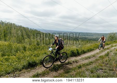 Revda Russia - July 1 2017: female and male athletes cyclists race in mountain trail during Regional competitions on mountain bike