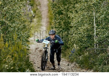 Revda Russia - July 1 2017: man cyclist with sports bicycle walk uphill during Regional competitions on mountain bike