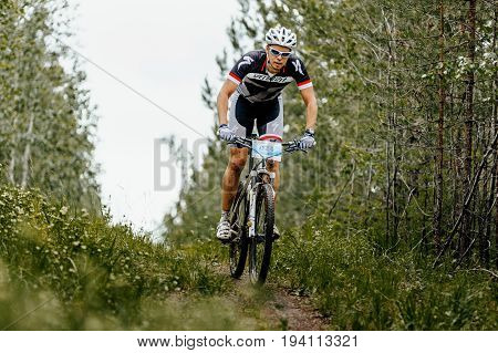 Revda Russia - July 1 2017: young male cyclist riding along a forest trail during Regional competitions on mountain bike