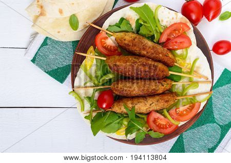 Minced meat on skewers - lula kebabs on a plate with fresh vegetables and greens on a white background. Top view. A traditional Central Asian dish.