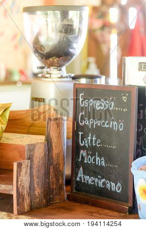 list of coffee menu on chalkboard (espresso cappuccino latte mocha americano) in coffee shop handmade cafe decoration on counter top