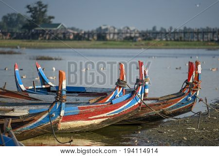 group of traditional boat in Taungthaman Lake near the U Bein Bridge famous landmark and tourist attraction of Amarapura Township Mandalay Myanmar (Burma)