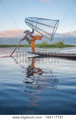 NYAUNGSHWE MYANMAR - DECEMBER 18 2016 : reflection of Burmese Intha fisherman with traditional fishing net on the boat in Inle.