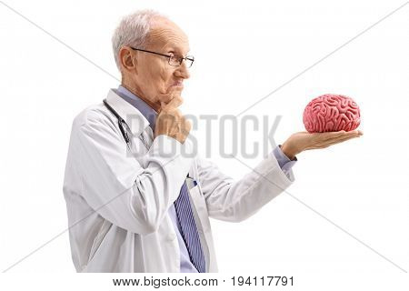 Pensive elderly doctor looking at a brain model isolated on white background