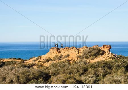 La Jolla USA - March 9 2014: Torrey Pines cliff in pacific ocean in San Diego California with people standing on top on trail