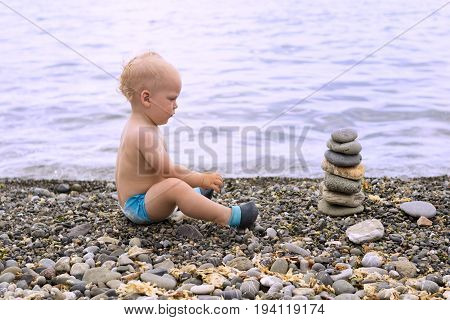 Tranquil Toddler Meditating On The Sea Beach. Cute Baby Boy Relaxing And Looking To The Stone Pyrami