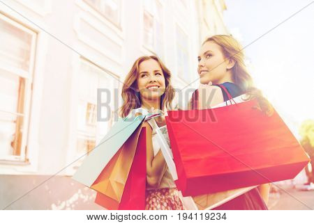 sale, consumerism and people concept - happy young women with shopping bags walking along city street and looking back