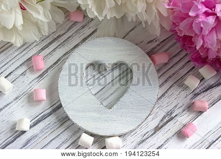 Peonies Flowers Pink With White Wooden Heart Marshmallow On A White Wooden Background - Stock Image.