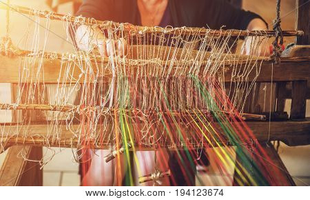 Craftsperson Woman working behind an old wooden loom in the sunlight in workshop
