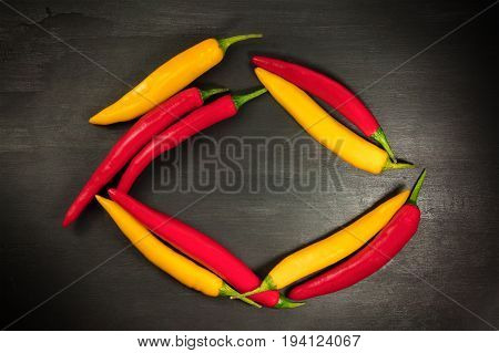 Red and yellow chilli peppers forming a frame on a black texture, shot from above with a place for text