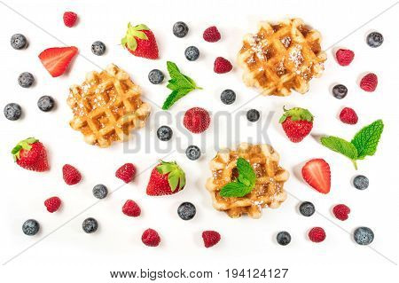 A photo of Belgian waffles with fresh fruit and mint leaves, shot from above on a white background