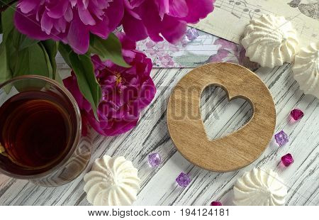 Peonies Flowers Pink Glass Of Tea With Brown Wooden Heart Marshmallow On A White Wooden Background -