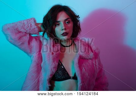 Young brunette posing in black lace bra and pink fur coat in neon lights.