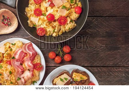 Scrambled eggs in a pan, on a plate, and on slices of bread, with cherry tomatoes, bacon, parsley, and cheese, shot from above on a rustic background with a place for text