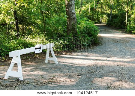 An arrow is taped onto a white wooden barrier showing the runners of a race which way to go in the woods
