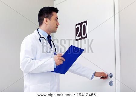 clinic, people, health care and medicine concept - doctor with clipboard opening hospital ward door