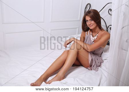 Romantic Beautiful Smiling Woman With Long Legs Posing In Fashion Dress On The Bed And Looking Seduc