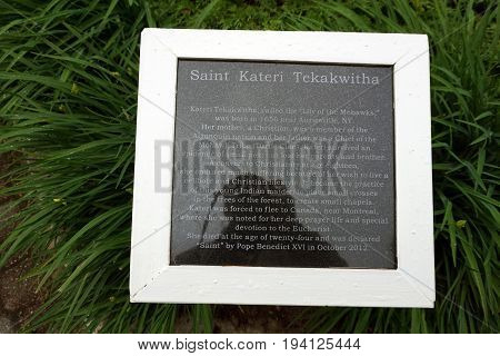 INDIAN RIVER, MICHIGAN / UNITED STATES - JUNE 18, 2017: A granite plaque at the Cross in the Woods Roman Catholic National Shrine describes the life of Saint Kateri Tekakwitha, called the